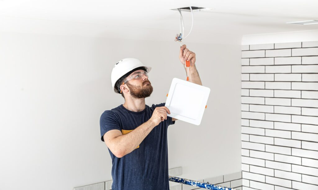 Electrician Builder at work, installation of lamps at height.