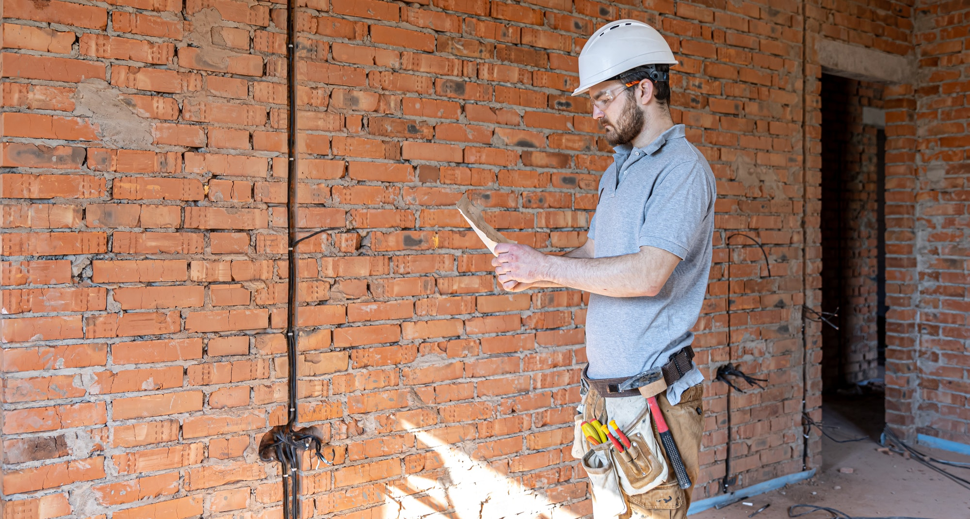 An electrician contractor examines a blueprint at a construction site.