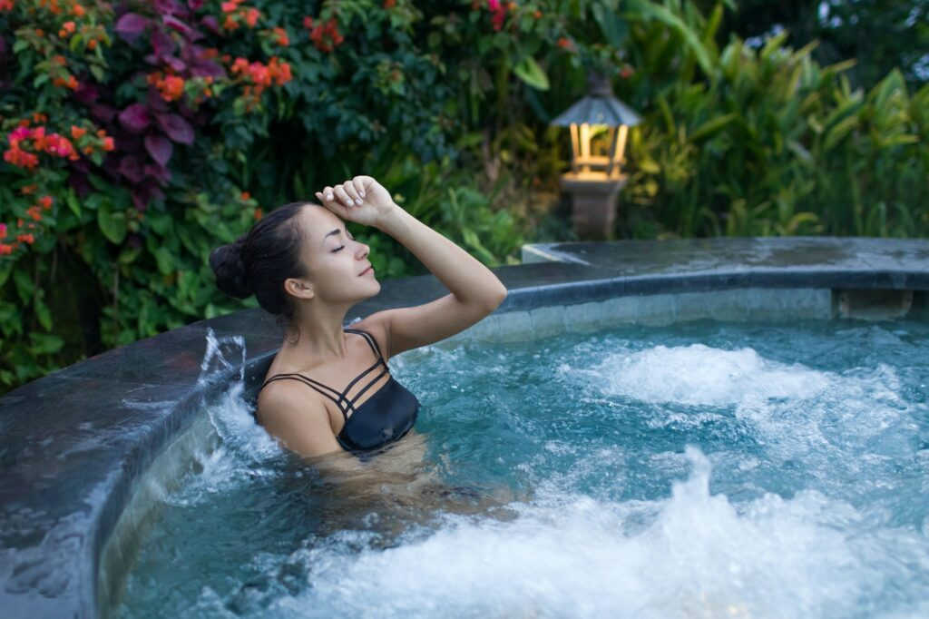 Young woman relaxing in jacuzzi spa in luxury hotel